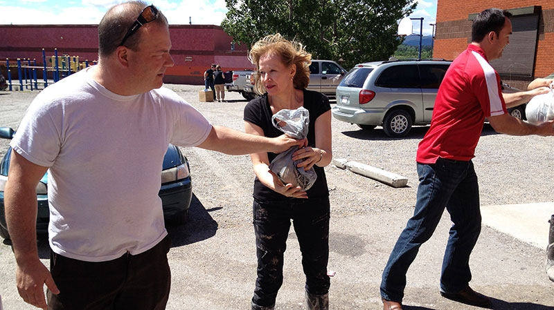 Lauren Harper is lending a helping hand by unloading trucks in Morley, Alta., on Wednesday, June 26, 2013. (Darin Saarela \ CTV News)