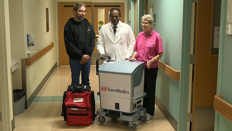 Dr. Jayan Nagendran stands with lung transplant patient Joyce Werk beside mobile lung machine Wednesday, June 26.