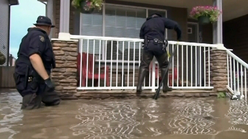 RCMP officers are shown in this image from video going door-to-door in search of High River residents trapped by flooding, on Wednesday, June 26, 2013. (RCMP)