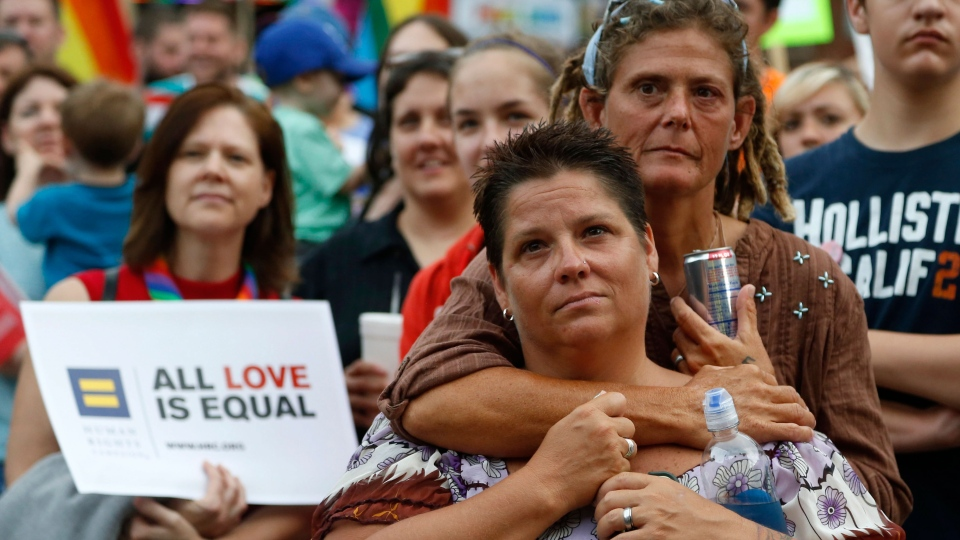 Jennifer Bryce, foreground, and her partner Renee Hendricks listen to speakers during a rally in the Boystown neighborhood of Chicago, Wednesday, June 26, 2013. (AP / Charles Rex Arbogast)