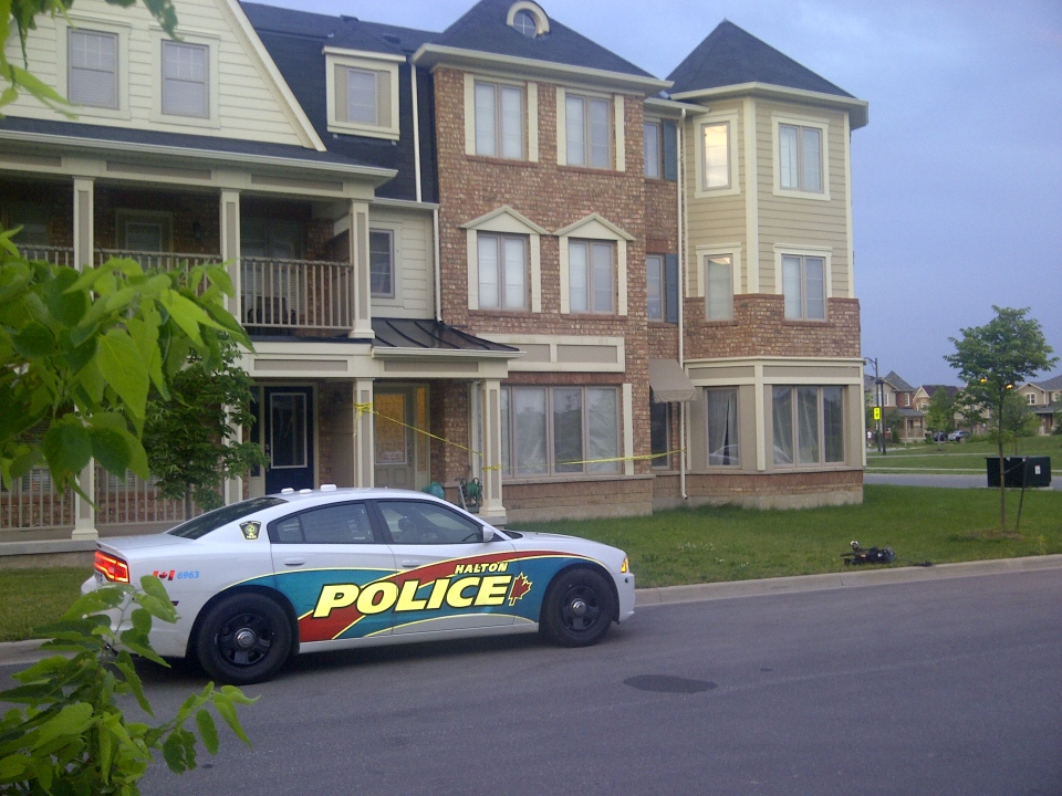 A police car is shown outside a residence in Milton, Ont., where a two-year-old boy died after being left in a car for a 'significant' amount of time.