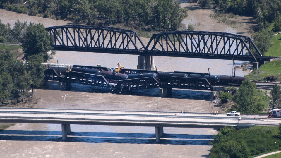 Crews work at the scene of a rail bridge collapse and railcars derailment over the Bow River, southeast of downtown Calgary, Alberta on Thursday, June 27, 2013. (Larry MacDougal / THE CANADIAN PRESS)
