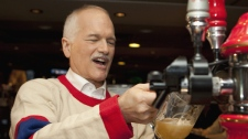 NDP Leader Jack Layton pours a beer behind the counter of a sport bar after watching the first period of the Montreal Canadiens and Boston Bruins NHL game on television Thursday, April 14, 2011 in Montreal. (THE CANADIAN PRESS/Jacques Boissinot)