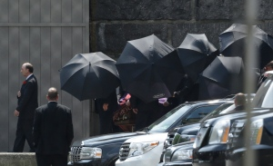 Men hold umbrellas as pallbearers walk with a casket containing the body of actor James Gandolfini at Cathedral Church of Saint John the Divine after funeral services for Gandolfini, Thursday, June 27, 2013, in New York. (AP / Julio Cortez)