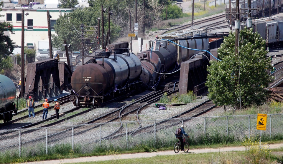 Crews work to stabilize a Canadian Pacific freight train as is sits derailed on a failing bridge over the Bow River in Calgary, Alta., Thursday, June 27, 2013. (Jeff McIntosh / THE CANADIAN PRESS)
