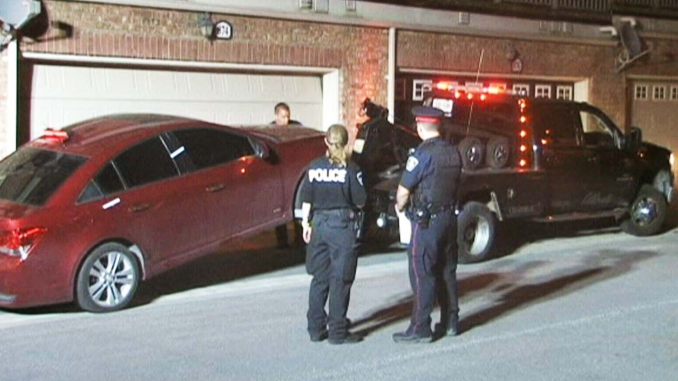 Police officers stand in front of a car about to be towed in Milton, Ont. on Wednesday, June 26, 2013. (CTV National News)