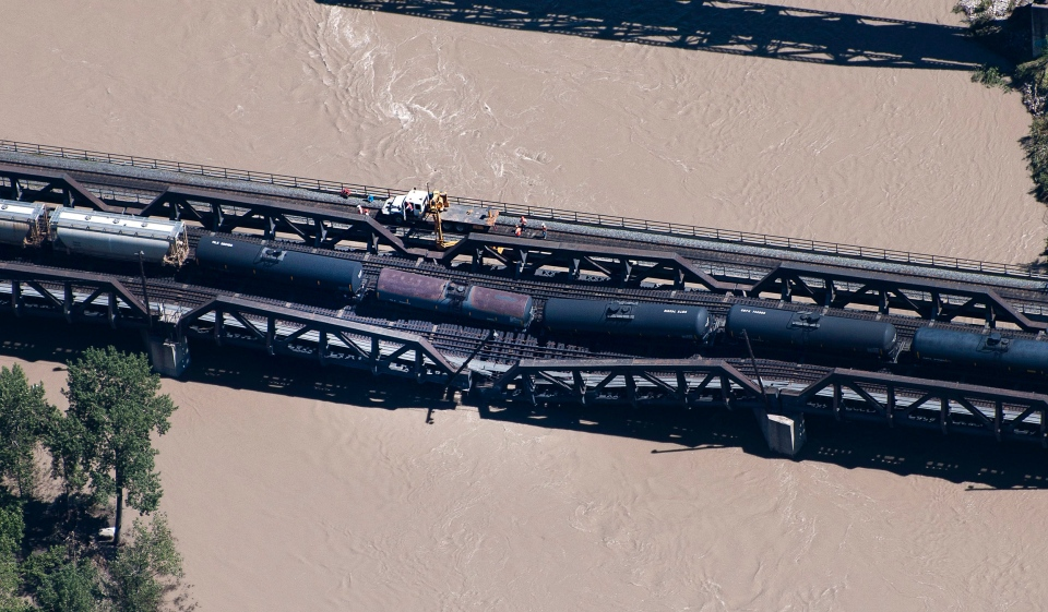 Crews work at the scene of a rail bridge collapse and rail car derailment over the Bow River, southeast of downtown Calgary, on Thursday, June 27, 2013. (Larry MacDougal / The Canadian Press)