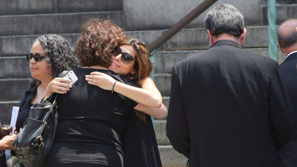 Actress Jamie Lynn Sigler, center, is embraced as she leaves the Cathedral Church of Saint John the Divine after the funeral service for James Gandolfini, Thursday, June 27, 2013 in New York. (AP / Mary Altaffer)