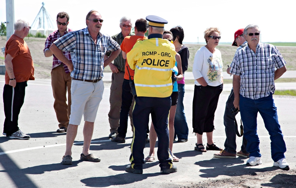 Frustrated evacuated residents speak with media following a press conference about the timeline for residents to re-enter the town of High River, Alta., on June 26, 2013. (Jordan Verlage / THE CANADIAN PRESS)