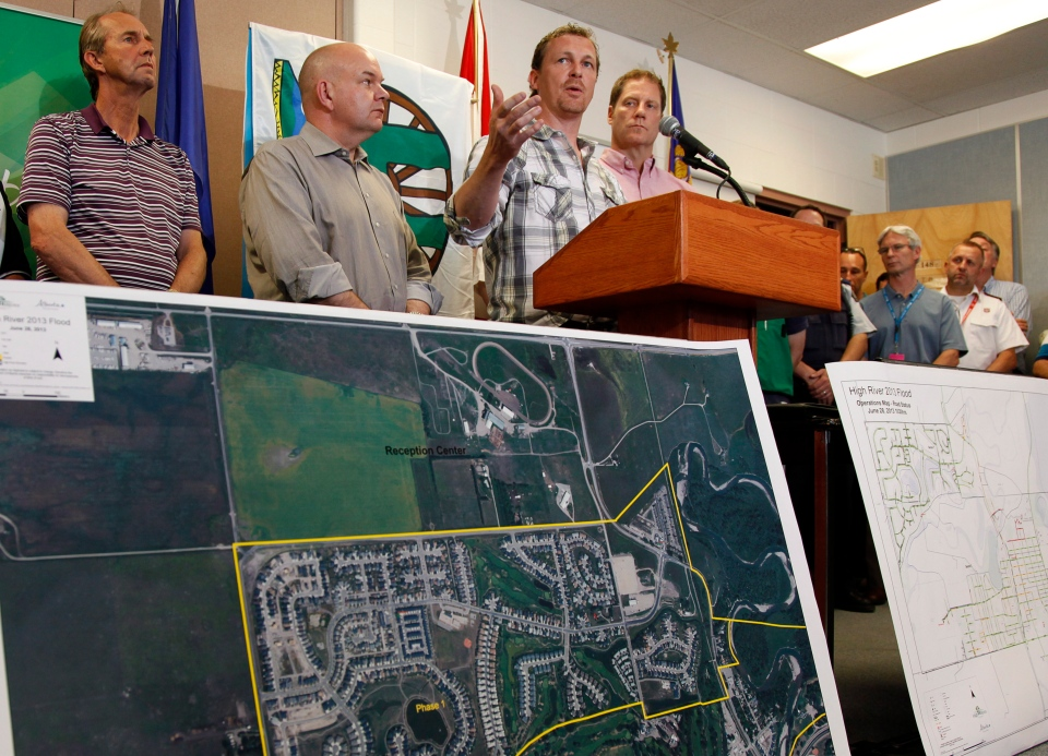 Doug Griffiths, centre, Alberta Minister of Municipal Affairs, announces that residents of High River will be allowed back into their homes in stages at a news conference in High River, Alta., Friday, June 28, 2013. (Jeff McIntosh / THE CANADIAN PRESS)