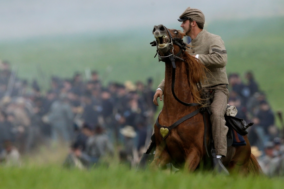A mounted Confederate re-enactor takes part in a demonstration of a battle during ongoing activities commemorating the 150th anniversary of the Battle of Gettysburg, at Bushey Farm in Gettysburg, Pa., Friday, June 28, 2013. (AP / Matt Rourke)