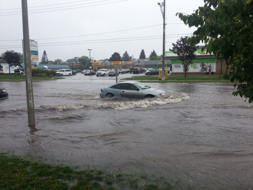 A car sits trapped in flash flood waters on Weber Street East in Kitchener, Ont., on Friday, June 28, 2013. (Courtesy Landon Metcalf)