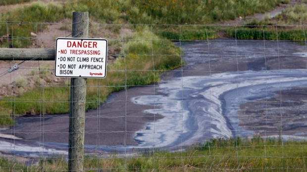 Tailings drain into a pond at the Syncrude oilsands mine facility near Fort McMurray, Alta., July 9, 2008. (Jeff McIntosh THE CANADIAN PRESS)