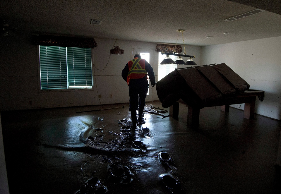 A safety inspector walks through muck to inspect the basement of a flood-damaged home in High River, Alta., Friday, June 28, 2013. (Chris Schwarz / Government of Alberta)