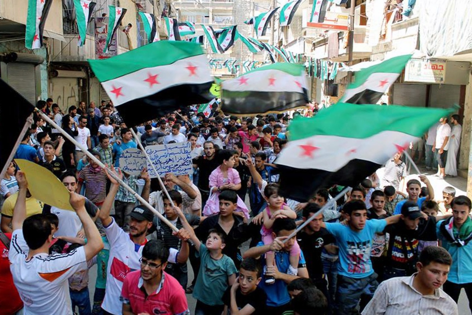 Anti-Syrian regime protesters hold Syrian revolution flags during a demonstration in the neighborhood of Bustan Al-Qasr in Aleppo, Syria, Friday, June 28, 2013. (Aleppo Media Center)