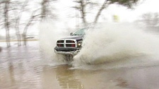 A truck creates a huge splash as it drives on a flooded road near Melita, Man., on Saturday, April 16, 2011.
