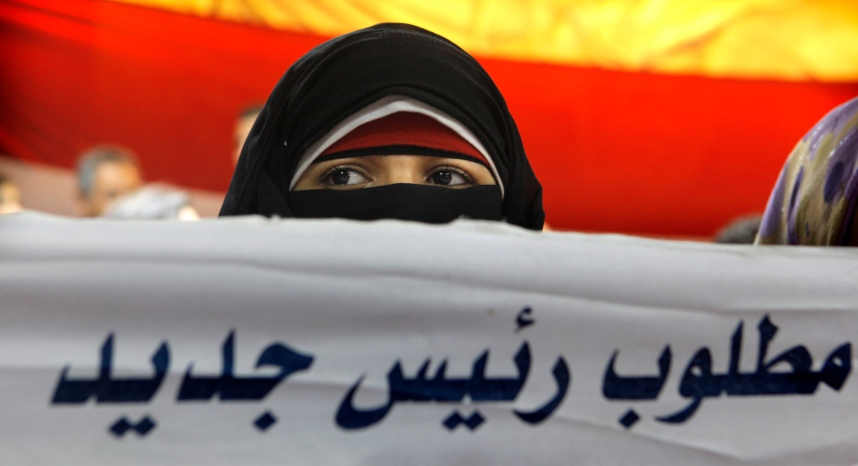 A veiled Egyptian woman holds a banner with Arabic reading, 'we need a new president', during a press conference by the youth group leading the campaign against Egypt's president in Cairo, Saturday, June 29, 2013. (AP / Amr Nabil)