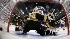 In this photo taken with a fisheye lens, Boston Bruins goalie Tim Thomas, foreground, looks behind as a shot by Montreal Canadiens' Mathieu Darche, right, goes in for a goal during the first period in Game 2 of a first-round NHL Stanley Cup playoffs hockey series in Boston, Saturday, April 16, 2011. (AP Photo/Winslow Townson)