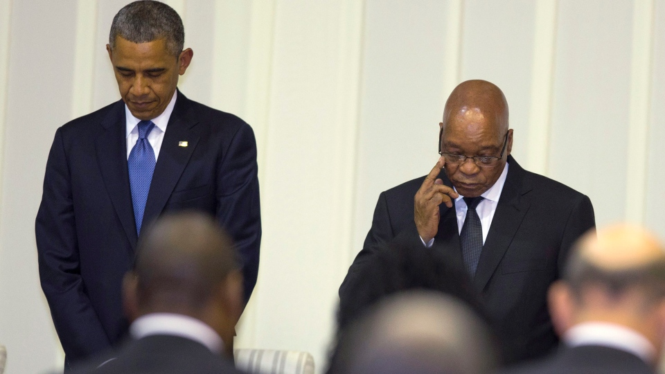 U.S. President Barack Obama, left, stands for a moment of silence for Nelson Mandela during an official dinner with South African President Jacob Zuma at the Presidential Guest House on Saturday, June 29, 2013, in Pretoria, South Africa. (AP / Evan Vucci)