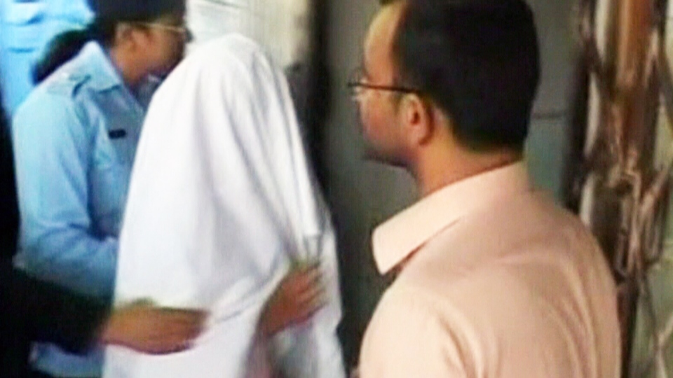 Shown with her face covered, Rimsha Masih is escorted in Pakistan in this undated photo from video. (CTV National News)