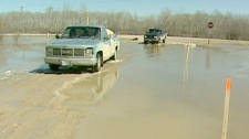Two cars are seen driving on a flooded road in Winnipeg, M.B., Sunday, April 17, 2011.