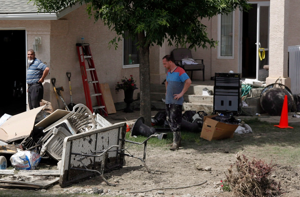 Residents clean up their home in High River, Alta., Saturday, June 29, 2013. (Jeff McIntosh / THE CANADIAN PRESS)