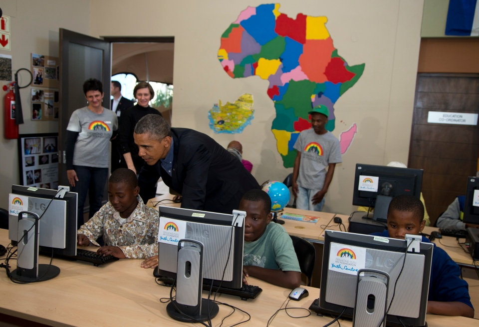 U.S. President Barack Obama looks at a project prepared by students at the Demond Tutu HIV Foundation Youth Center, during his visit to Cape Town, South Africa, Sunday, June 30, 2013. (AP / Evan Vucci)