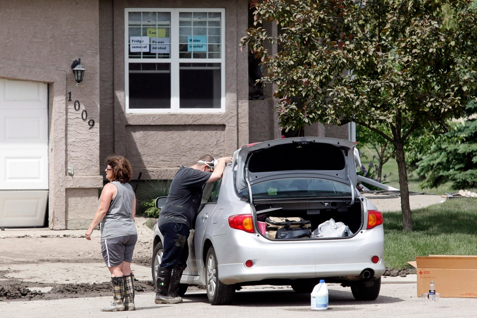 A resident rests on his car as he cleans up his home in High River, Alta., Saturday, June 29, 2013. (Jeff McIntosh / THE CANADIAN PRESS)