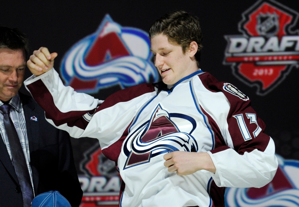 Nathan MacKinnon, a center, pulls on a Colorado Avalanche sweater after being chosen 1st overall in the first round of the NHL hockey draft, Sunday, June 30, 2013, in Newark, N.J. (AP / Bill Kostroun)
