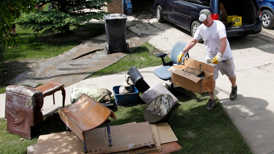 A resident cleans up his home in High River, Alta., Saturday, June 29, 2013. (Jeff McIntosh / THE CANADIAN PRESS)