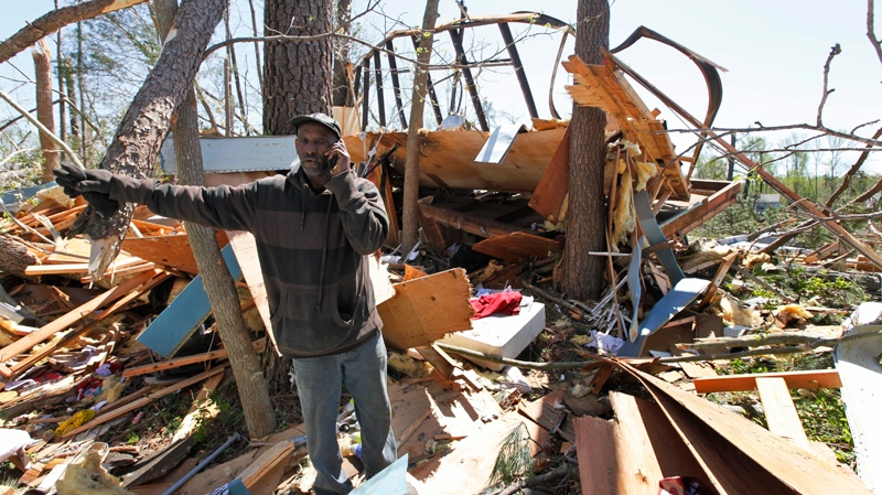 Randy Cook talks on the phone as he sorts through debris of his sister's home after a tornado that swept through the area Saturday night in Gloucester, Va., Sunday, April 17, 2011. (AP / Steve Helber)