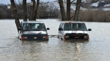 Vans stand in high water in the Qu'Appelle Valley northwest of Regina on Sunday April 17, 2011. (Roy Antal / THE CANADIAN PRESS)