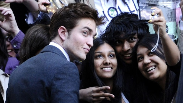 "Actor Robert Pattinson takes pictures with fans at the premiere of ""Water For Elephants"" at the Ziegfeld Theater on Sunday, April 17, 2011, in New York. (AP Photo/Peter Kramer)"