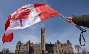 A Canadian flag attached to a ski pole is waved on Parliament Hill in Ottawa on Monday, April 15, 2013. (Sean Kilpatrick / THE CANADIAN PRESS)
