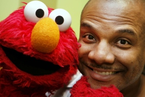 This file photo from Aug 16, 2006 shows Kevin Clash, who was the voice and movements behind Sesame Street's Elmo, posing for a picture with Elmo in New York. (AP / Seth Wenig, File)