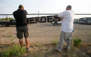 Two men place a hero sign in front of Prescott Fire Station #7 on Monday, July 1, 2013, in Prescott, Ariz. Tributes continue to pour in for 19 firefighters who lost their lives while fighting wildfires that continue to rage across Arizona. (David Wallace / The Arizona Republic)