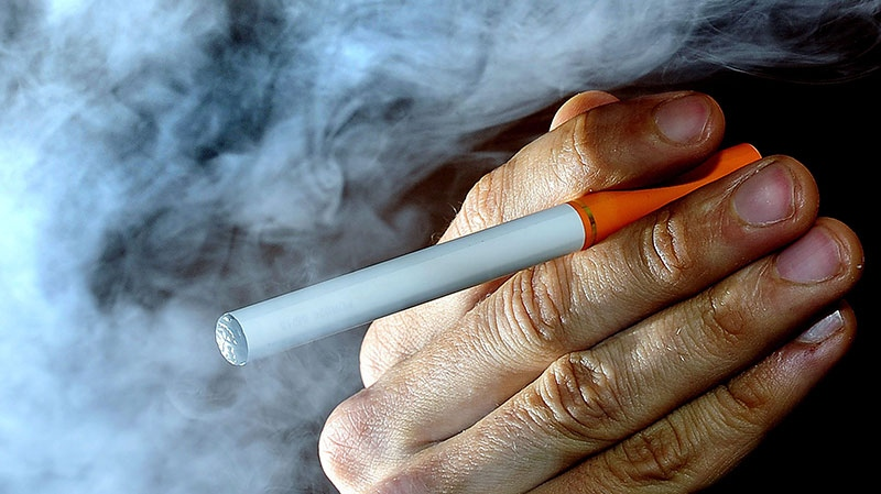 A person poses with an electronic cigarette, or e-cigarette, Wednesday June 12, 2013. (AP / Tim Ireland)