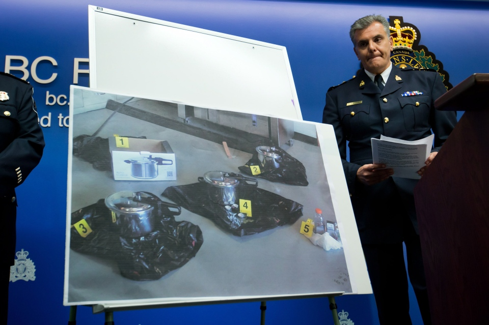 RCMP Assistant Commissioner Wayne Rideout looks at a photograph of pressure cookers that RCMP say two people intended to use as explosive devices, during a news conference to announce terrorism charges in Surrey, B.C., on Tuesday, July 2, 2013. (Darryl Dyck / THE CANADIAN PRESS)