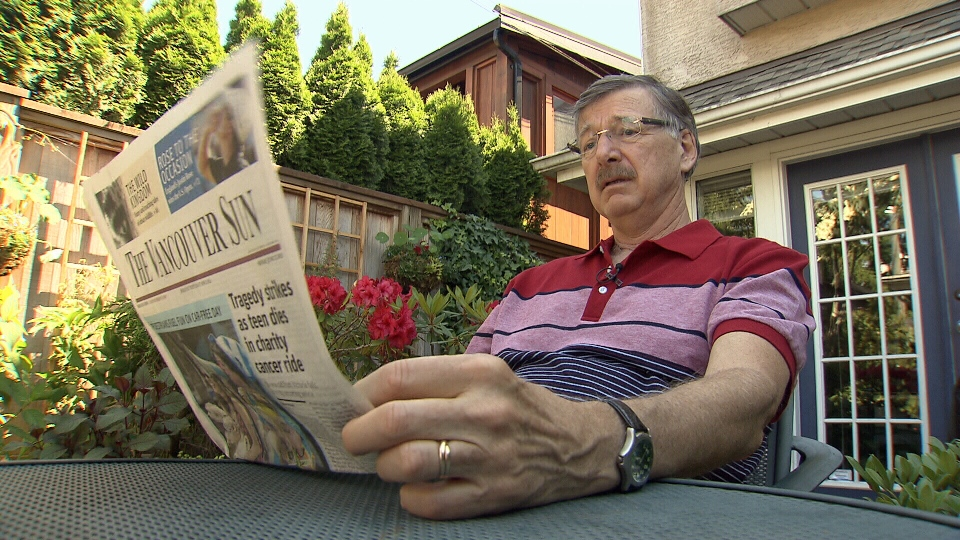 Langara journalism professor Ross Howard reads a print copy of the Vancouver Sun following massive staff reductions at the paper. (CTV)
