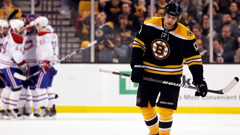 Boston Bruins left wing Milan Lucic, right, skates back to the bench as the Montreal Canadiens, background left, celebrate a goal during the second period of Game 2 of a first-round NHL Stanley Cup playoffs hockey series in Boston, Saturday, April 16, 2011. (AP Photo/Winslow Townson)