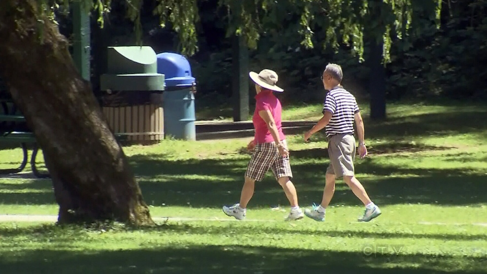 A couple takes a walk in Abbotsford,  B.C., Tuesday, July 2, 2013.