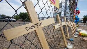 Crosses with the names of the deceased lean on a fence outside Fire Station 7 in Prescott, Ariz. on Tuesday, July 2, 2013 in a makeshift memorial for the 19 Granite Mountain Hotshots who were killed by an out-of-control blaze near Yarnell, Ariz. on Sunday. (AP / The Arizona Republic, Tom Tingle)