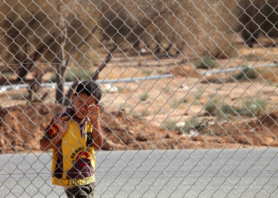 A Syrian refugee boy stands watches the arrival of the Italian delegation of the Italian foreign minister Emma Bonino to Zaatari refugee camp near the Syrian border, in Mafraq, Jordan, Tuesday, June 25, 2013. (AP / Mohammad Hannon)