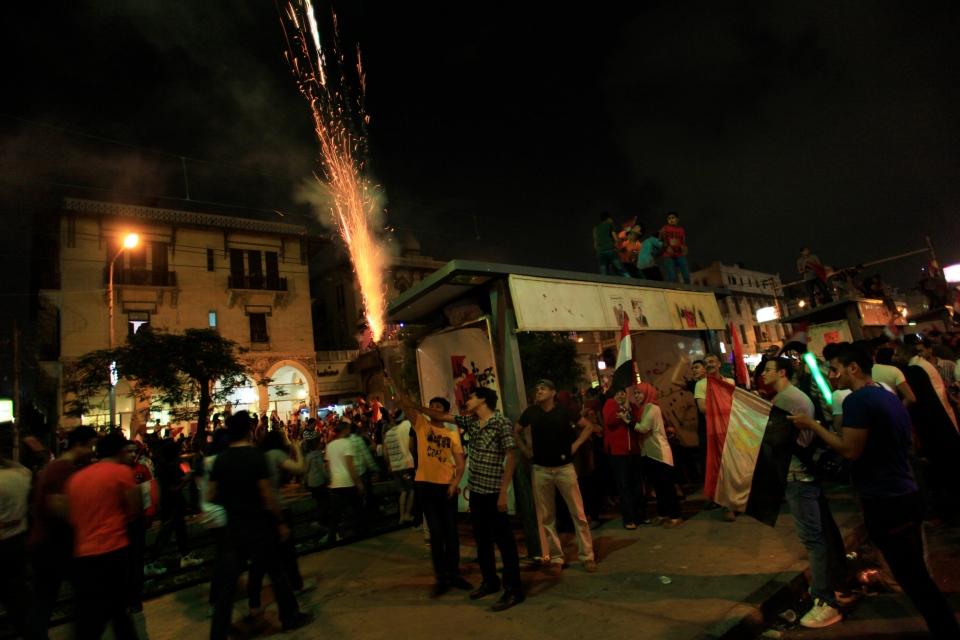 Opponents of Egypt's Islamist leader Mohammed Morsi light fireworks as they celebrate outside the presidential palace in Cairo, Egypt, Wednesday, July 3, 2013.  (AP / Khalil Hamra)