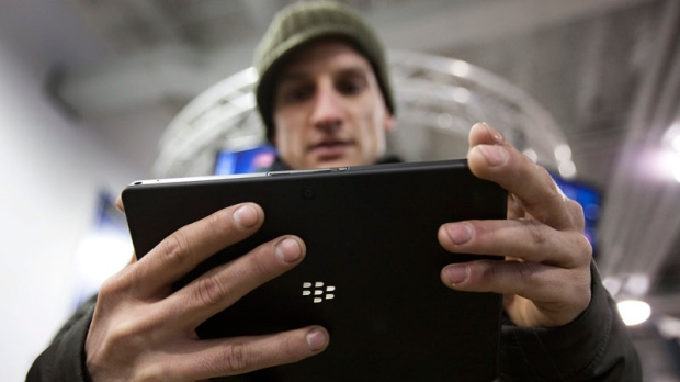 A customer plays with the Blackberry Playbook during the tablet's launch in Toronto Tuesday, April 19, 2011. (Darren Calabrese / THE CANADIAN PRESS)