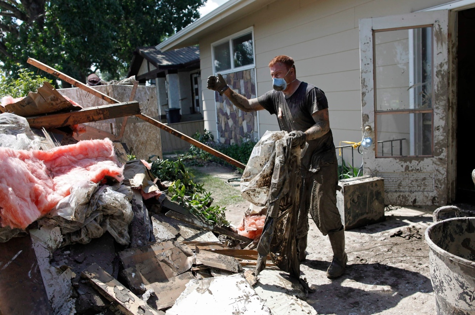 Yahya Abougoush helps clean up his parents' house in High River, Alta., Wednesday, July 3, 2013. (Jeff McIntosh / THE CANADIAN PRESS)