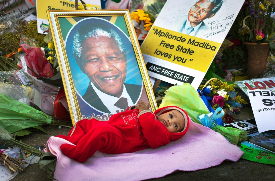Oamohetswe Mabitsela, 4 months old, is placed by his mother next to a picture of Nelson Mandela for her to take a photograph of him with her camera phone, outside the Mediclinic Heart Hospital where former South African President Nelson Mandela is being treated in Pretoria, South Africa, Thursday, July 4, 2013. (AP / Ben Curtis)
