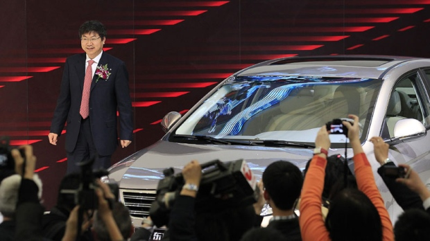 Yin Tongyao, CEO of Chery Automobile stand next to a car unveiled during a Chery presentation on the press day at the Shanghai International Auto Show Tuesday, April 19, 2011 in Shanghai, China. (AP Photo/Eugene Hoshiko)