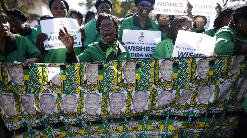 Women of the ANC women league sing and hold posters in support of former South African President Nelson Mandela at the entrance of the Mediclinic Heart Hospital where Nelson Mandela is being treated in Pretoria, South Africa, Thursday, July 4, 2013. (AP / Markus Schreiber)