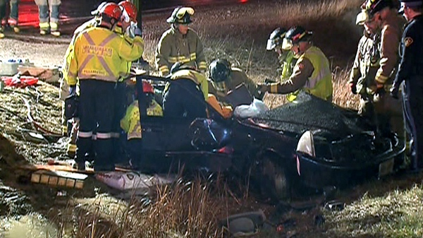 Firefighters work to free a woman from her car at the crash site on Highway 427, early Friday, April 20, 2011.